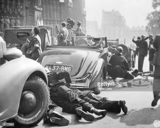 French gendarmes take shelter behind traffic as German snipers fire in a crowded section of Paris after the city was liberated by the Americans