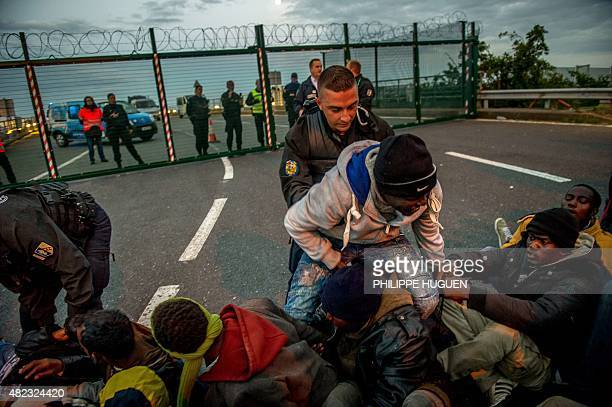 French gendarmes try to separate migrants on the Eurotunnel site near the boarding docks in Coquelles near Calais northern France on late July 29...