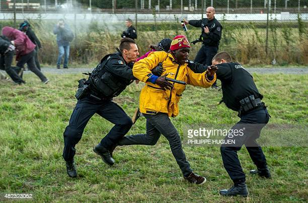 French gendarmes try to stop migrants on the Eurotunnel site in Coquelles near Calais northern France on late July 29 2015 One man died Wednesday in...