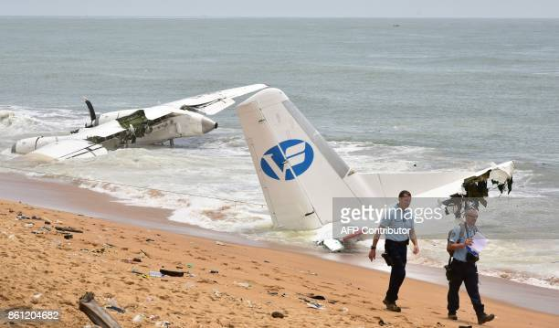 French Gendarmes walk on the beach of PortBouet in Abidjan as they look at the wreckage of a cargo plane that crashed off Ivory Coast killing four on...