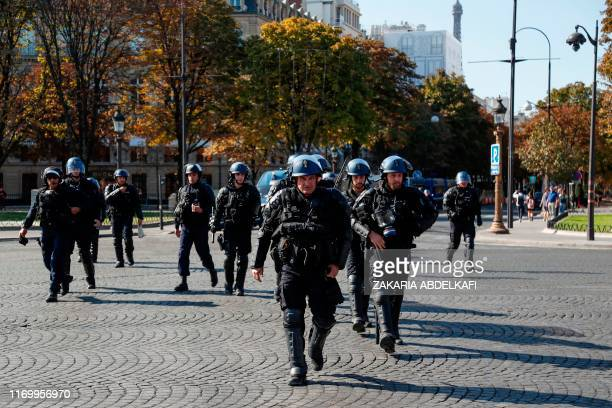 """French gendarmes walk on the Champs Elysees avenue during an anti-government demonstration called by the """"yellow vest"""" movement, on September 21,..."""