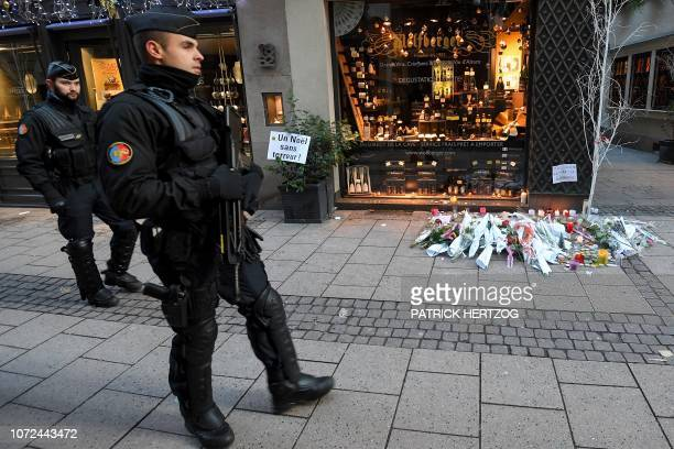 French gendarmes walk past flowers and candles laid in the street in tribute to the victims of a deadly shooting two days ago in central Strasbourg...