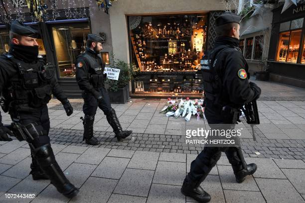 TOPSHOT French gendarmes walk past flowers and candles laid in the street in tribute to the victims of a deadly shooting two days ago in central...