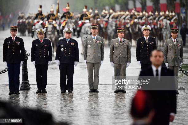 French generals and admirals stand guard behind French President at the tomb of the unknown soldier under the Arc de Triomphe landmark on top of the...