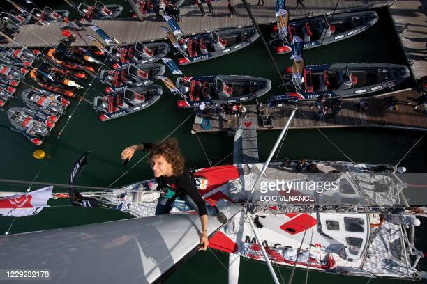 French German skipper Isabelle Joschke climbs on the mast of her Imoca 60 monohull MACSF on October 22, 2020 at the starting site of the 2020 edition...