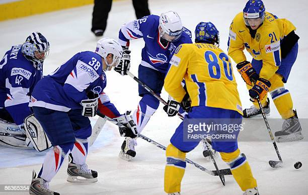 French goalkeeper Fabrice Lhenry with teammate Thomas Roussel and Benoit Quessandier tussle for the puck against Sweden's Mattias Weinhandl and his...