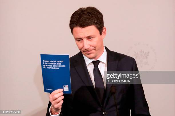 French Government's spokesperson Benjamin Griveaux holds up a document 'Bill on the taxation of large digital companies' during a press conference...