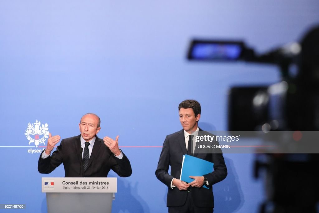 French Government's Spokesperson Benjamin Griveaux (R) listens to French Interior Minister Gerard Collomb speaking during a press conference about the new immigration law presented during the cabinet meeting earlier on February 21, 2018, in Paris. The government says the law balances 'efficiency' with 'humanity', offering faster asylum to refugees found to have fled conflict or repression. MARIN