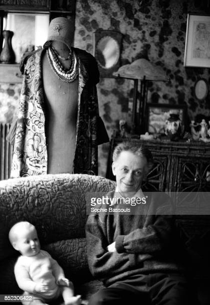 French graphic designer Robert Massin who is often called the father of expressive typography sits on a sofa next to a doll and dressmakers' dummy in...