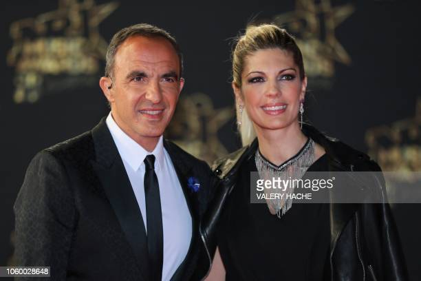 French Greek TV host Nikos Aliagas and his partner Tina Grigoriou poses on the red carpet upon his arrival to attend the 20th NRJ Music Awards...