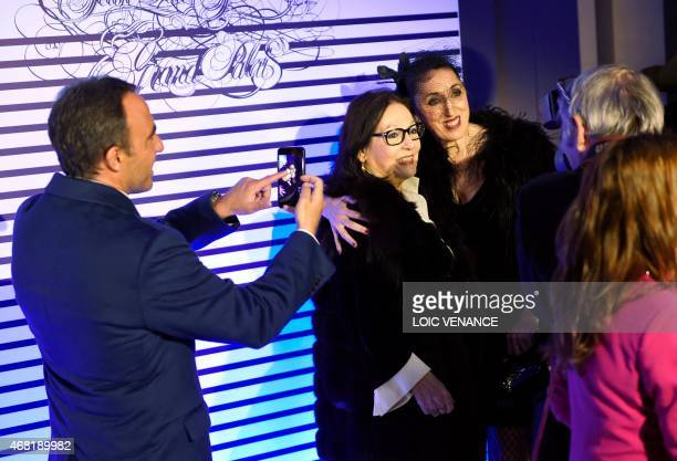 French Greek TV host Nikos Aliagas takes a picture of Greek singer Nana Mouskouri and Spanish actress Rossy de Palma as they arrive to attend a party...
