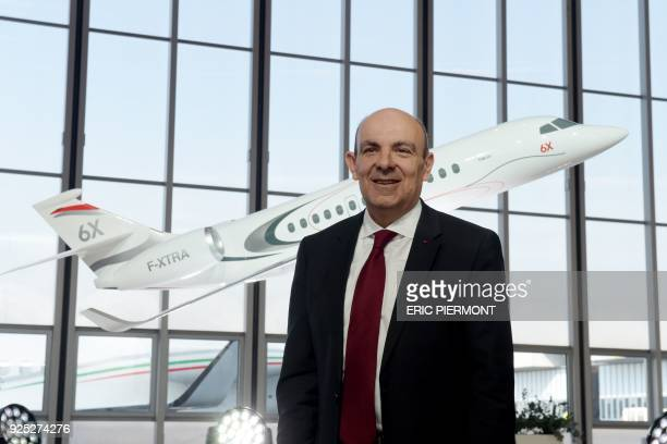 French group Dassault Aviation Chief Executive Eric Trappier poses in front of the model of the future Dassault's Falcon 6X jet during a press...