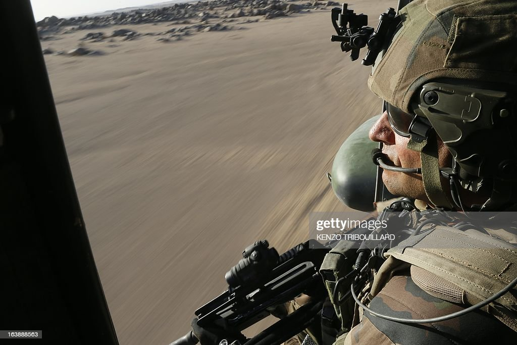 A French gunner sits in a Puma helicopter flying near Tessalit on March 17, 2013. A French corporal was killed tracking down jihadist fighters in their northern Mali mountain bastions, bringing to five the number of French deaths since Paris launched a military offensive in the country two months ago. Defence Minister Jean-Yves Le Drian said on March 17, 2013 the 24-year-old soldier was killed and three of his comrades wounded when their vehicle was struck by a roadside bomb blast in the Ifoghas mountains, without saying when it happened.