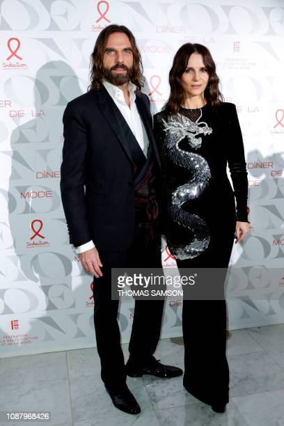 French hair stylist John Nollet and French actress Juliette Binoche pose during a photocall upon arriving to attend the Diner de la Mode fundraiser...
