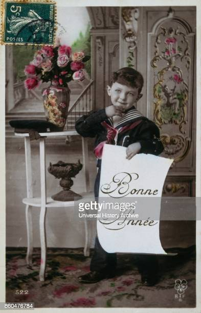 French Happy New Year postcard depicting a boy holding a paper saying happy new year circa 1900