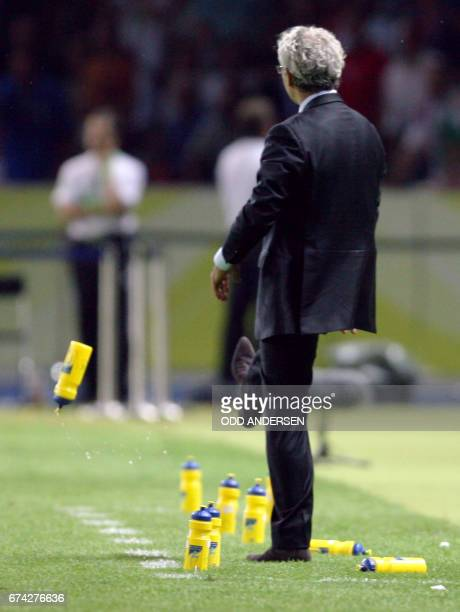 French head coach Raymond Domenech kicks a water bottom in frustration after French midfielder Zinedine Zidane received a red card for headbutting...