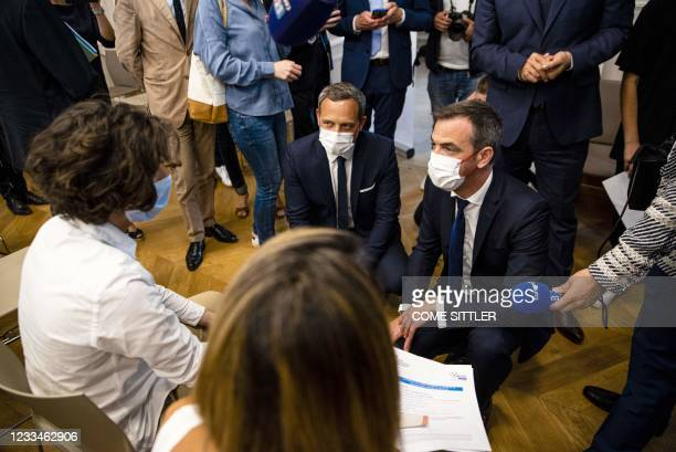 French Health Minister Olivier Veran and French Junior minister for Childhood and Family Affairs Adrien Taquet speak with nurses as they visit a...