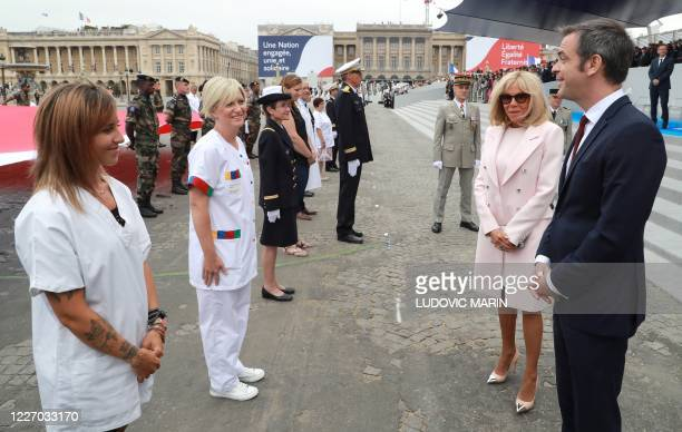 French Health Minister Olivier Veran and French President's wife Brigitte Macron speak to memembers of the medical staff at the end of the annual...