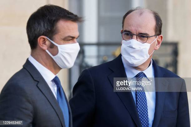 French Health Minister Olivier Veran and French Prime Minister Jean Castex wearing a face mask, leave after attending the weekly cabinet meeting at...