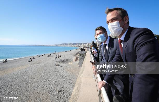 French Health Minister Olivier Veran and the Mayor of the city of Nice Christian Estrosi stand in front of the Mediterranean Sea after a visit at the...