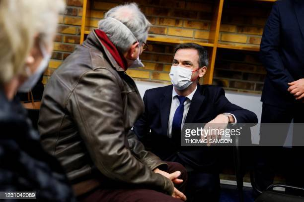 French Health Minister Olivier Veran speaks to people waiting to be vaccinated or with the AstraZeneca-Oxford Covid-19 vaccine or with the...