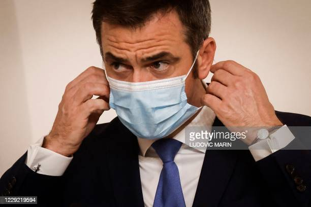 French Health Minister Olivier Veran takes off his protective facemask to deliver a speech during a press conference, at the Hotel Matignon, in...