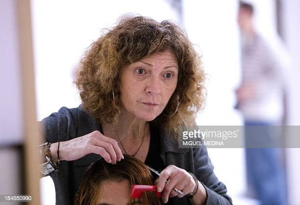 French heardresser Lucia Iraci owner of several barbershops for people in need makes a haircut for a client on october 22 2012 in Paris AFP PHOTO...