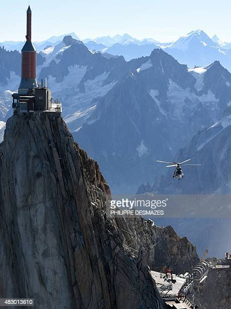 French helicopter 'Super Puma' transports a piece of steel that is to be part of the new 'Pipe' at the Aiguille du Midi peak on August 5 2015 in...