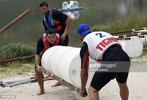 French hooker Guilhem Guirado and French fly half Remi Tales build a raft during a contest as part of the French rugby union team's training camp in...
