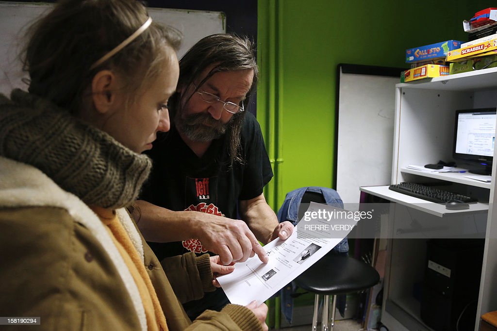 French host of 'Cultures du cœur', an association that distributes theatre tickets, and former homeless person Serge Peltier, prints theatre tickets for disadvantage people in Paris on December 10, 2012 at the '13 pour tous' association offices in the Massena shopping centre. Cultures du cœur, meaning culture of the heart, distibutes nightly between 600 and 700 theatre tickets to persons in need.