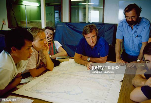 French humanitarian Dr Bernard Kouchner President of Doctors Without Borders looks over a map with rescue workers during a rescue operation of...