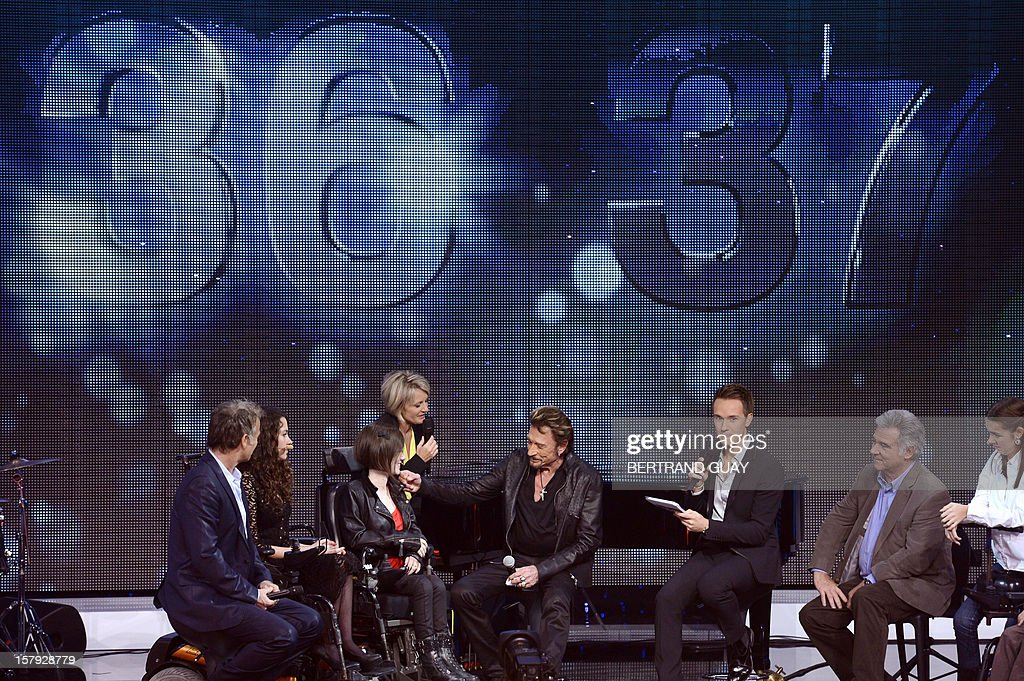 French humorist and godfather Franck Dubosc (L), TV hosts Sophie Davant (C, left), and French singer Johnny Hallyday (C) attend the 26th Telethon, France's biggest annual fund-raising event during 30 hours of live television transmission, on December 7, 2012 in Saint-Denis, north of Paris. The event, aiming at collecting funds for research on genetic diseases such as myopathy, a neuromuscular disease, will take place on December 7 and 8, 2012.