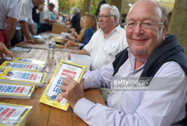 French humorist Bernard Mabille poses with his books during the 21th book fair La Foret Des Livres on August 28 2016 in ChanceauxprèsLoches central...