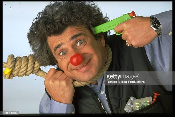 French humorist Michel Boujenah wearing a red clown nose mimes the happy suicide with a noose around his neck pills in his pocket and holding a...