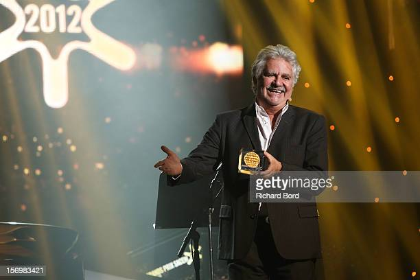 French humorist Roland Magdane poses onstage as he receives the 'Grand Prix de l'Humour' during the 'Grand Prix SACEM 2012' at Casino de Paris on...
