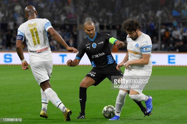 """French humourist Redouane Bougheraba fights for the ball with French-US former basketball player Tony Parker during the charity """"Heroes"""" football..."""