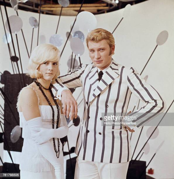 French husband and wife singers and actors Johnny Hallyday and Sylvie Vartan posed together wearing white flapper style period dress and white and...