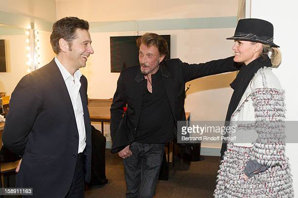 French impersonator Laurent Gerra talks with French rocker Johnny Hallyday and Hallyday's wife Laeticia in Gerra's dressing room following his one...