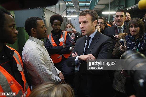 French independent presidential candidate Emmanuel Macron chats with participants in a training program for refugees at a train repair facility of...