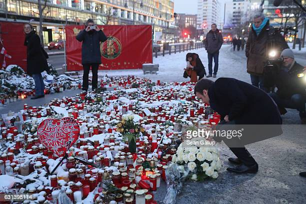 French independent presidential candidate Emmanuel Macron lays flowers at a memorial to the December 19 terror attack at Breitscheidplatz on January...