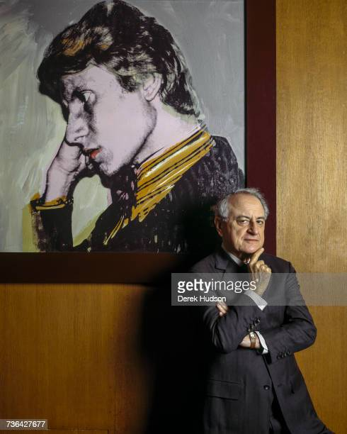 French industrialist and patron Pierre Bergé in his office at the Yves Saint Laurent headquarters with a portrait of SaintLaurent by Andy Warhol...