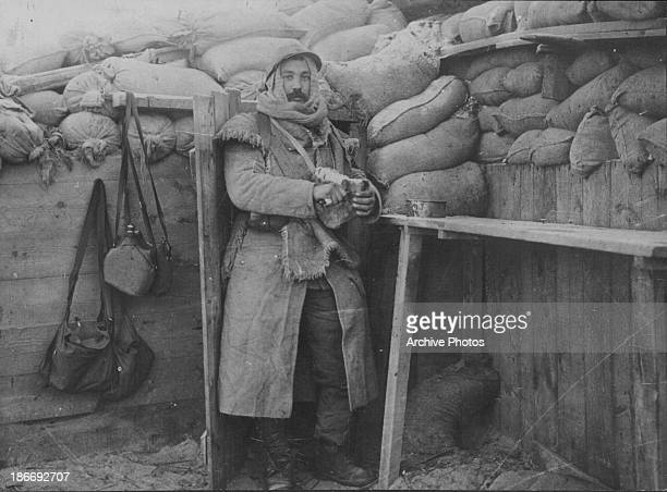 French infantryman, or Poilu, keeping warm in a trench during World War One, France, 1917.