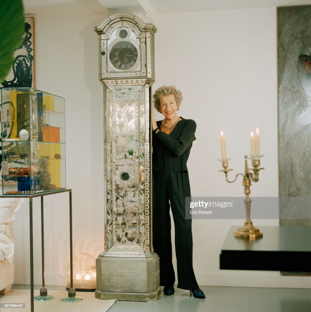 French Interior Designer Andree Putman Poses At Home With An 18th Century Mirror Pendulum Grandfather Clock