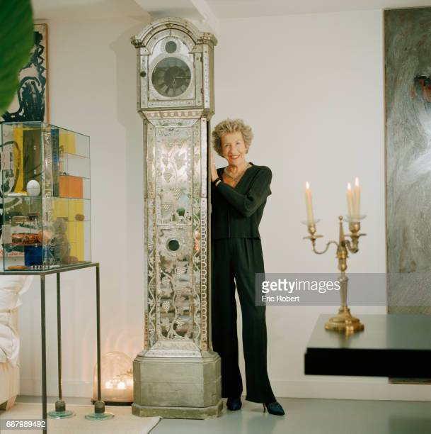 French interior designer Andree Putman poses at home with an 18th century mirror pendulum grandfather clock Putman has designed and decorated the...