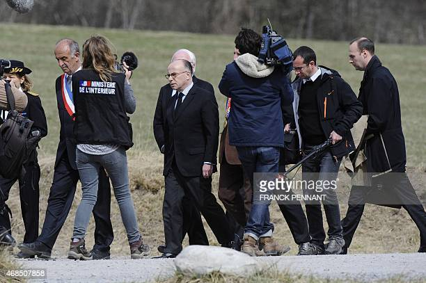 French Interior Minister Bernard Cazeneuve and officials leave after laying a wreath at the stele in memory of the victims of the Germanwings Airbus...