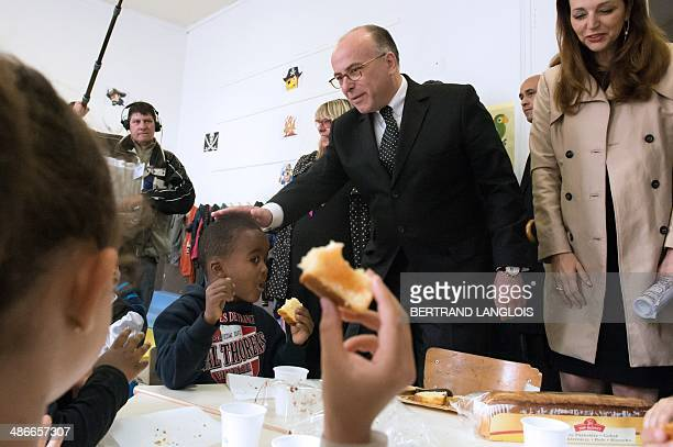 French Interior Minister Bernard Cazeneuve pats a boy on the head flanked by French rightwing opposition UMP party member of parliament and mayor of...