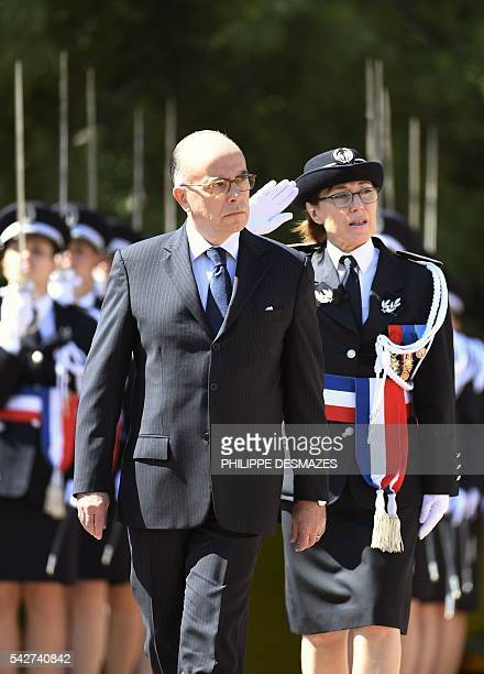 French interior minister Bernard Cazeneuve reviews the newly promoted police chiefs with school director Helene Martini during a ceremony of the 66th...