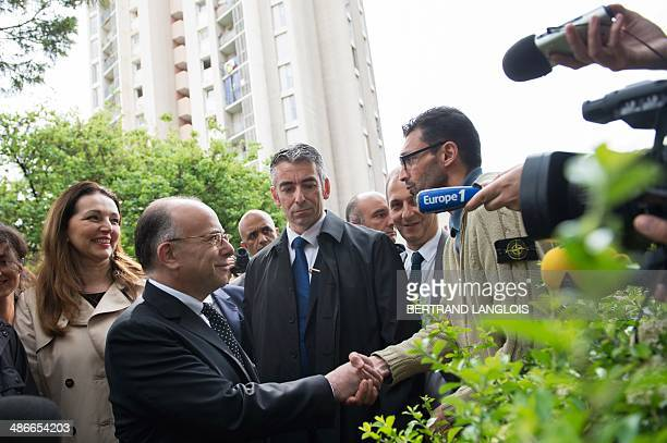 French Interior Minister Bernard Cazeneuve shakes hands with a resident flanked by French rightwing opposition UMP party member of parliament and...