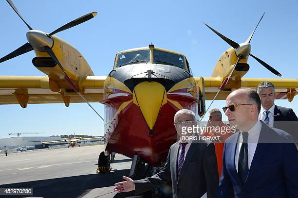 French Interior Minister Bernard Cazeneuve walks by a Canadair alongside with French Director of the water Bombardier air base of the Civil Security...