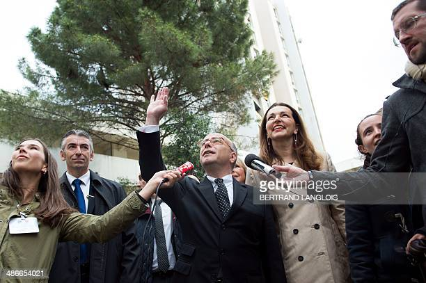 French Interior Minister Bernard Cazeneuve waves next to French rightwing opposition UMP party member of parliament and mayor of Marseille's sixth...